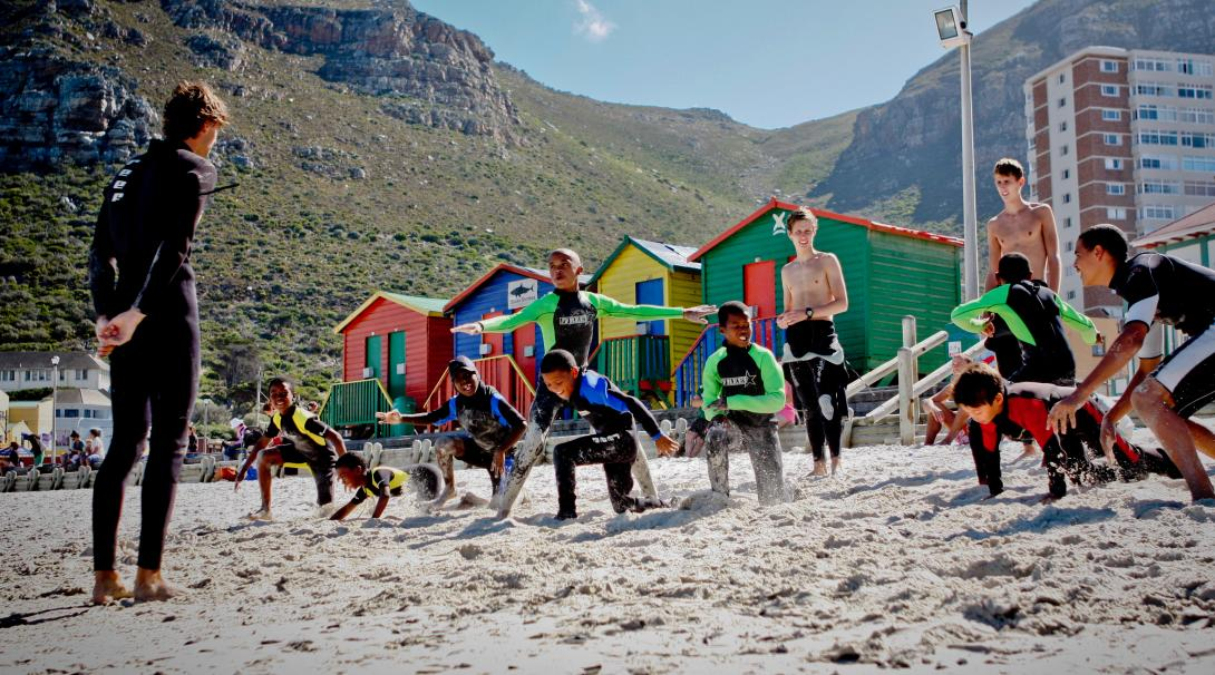 Stretching on the beach in a surfing project, South Africa